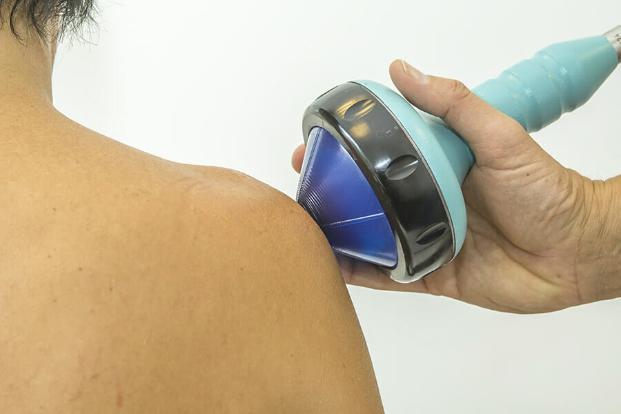physiotherapist in oakville doing shockwave to a patients shoulder