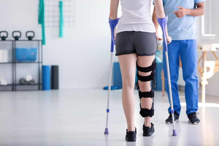 Oakville Physiotherapy post fracture rehab of an injured leg broken bone lady with brace and crutches learning to walk