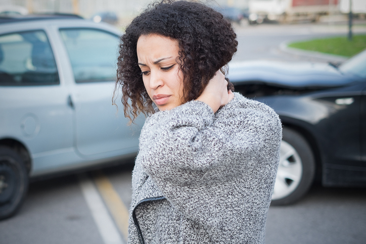 car accident treatment physiotherapy oakville , lady holding her neck after car accident in the back ground