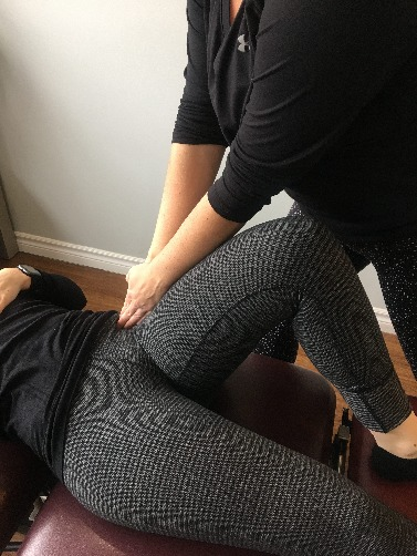 patient on her back with physiotherapist pushing into front of hip