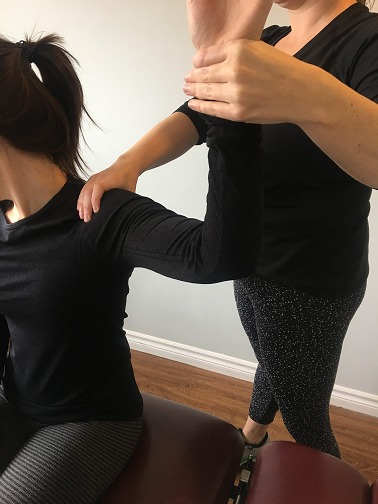 patient sitting while physiotherapist hold arm at an 90 degree angle and treats shoulder